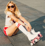 A looker leggy long-haired young blonde woman in a vintage roller skates, sunglasses, T-shirt shorts sitting on road. Eye-candy yo Royalty Free Stock Image