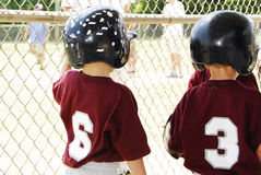 On Lookers. Two young t-ball players looking out through the fence at their ball game Royalty Free Stock Image