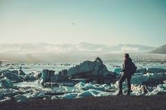 Lookig do explorador da mulher na lagoa de Jokulsarlon, Islândia foto de stock
