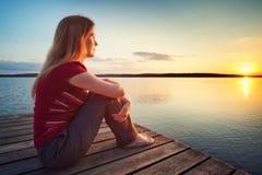 Lookin молодой женщины на заходе солнца Стоковое Изображение RF