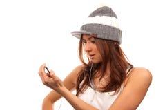 Lookin femenino en el teléfono celular en auriculares Imagen de archivo