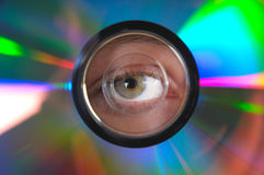 Looking through. Someone looking through the circle hole in side a compact disc.  With all the colours reflecting around the cd Stock Photos