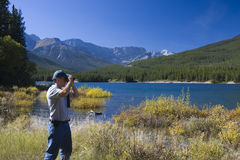 Looking. On a sunny autumn afternoon on the shore of Upper Kananaskis Lake, a man looks through binoculars Royalty Free Stock Images