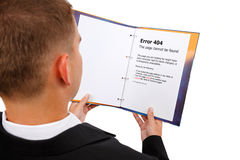 Looking at 404 error page in book. Man looking at book, error 404 page displayed. Metaphoric view of a missing document royalty free stock photography