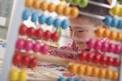 Looking Through Abacus at Boy Solving a Puzzle Royalty Free Stock Photography