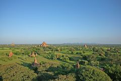 The red brick stupas and pagodas of the Bagan plains stretch out to the horizon. Looking across the Bagan Archaeological Zone spread over 26 square miles of lush Stock Photos