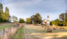 Looking across farm field to an old chapel near Victoria, BC Royalty Free Stock Image