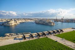 Guns across Malta`s Grand Harbour; views of Birgu and Senglea. Looking across the Grand Harbour from the Saluting Gallery near the Upper Baraka Gardens in Royalty Free Stock Images
