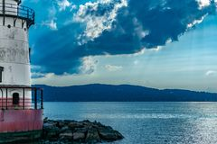Looking across the Hudson River toward the Jersey Shore, with the Sleepy Hollow Lighthouse to the left, with rays of stock photo