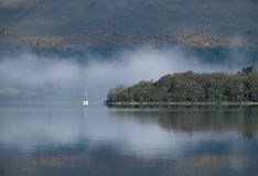 Looking across Loch Lomond towards Inchmurrin and a yacht Stock Images