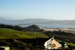 Looking across Oceana Marin towards Tomales Bay. Over modern houses and green fields on a hazy day. Sand dunes in the distance Royalty Free Stock Photo