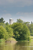 Looking across a river at grain silos Royalty Free Stock Images