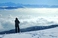 Looking across the valley. A skier, high on a slope in the Swiss Jura mountains in winter, takes a break from skiing and gazes across to the French Alps. The Stock Photography