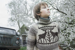 Looking ahead teenager in woolly vintage deer sweater outdoors in blooming fruit garden at old log house Stock Photo
