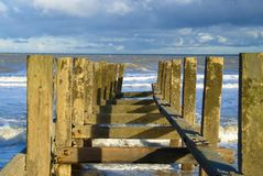 Looking along the sea defence`s. Sea defence`s known as groyne`s which are sturdy wooden built structures to stop beach erosion on the north Norfolk coast Stock Photo
