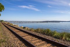 Looking along train line to White Rock pier, BC. A trainline follows the seafront at White Rock, BC, Canada.  A wooden pier for pedestrians extends 1/2km 1650 Stock Photo