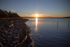 Looking along White Rock beach to dramatic winter sunrise. Looking east along the shoreline towards the glacial erratic - the white rock - that gives the town Stock Photos