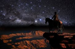Looking at the amazing universe. Cowboy on his horse, looking at a mountains landscape, whereas a magnificent view  of the universe rises in front of him Royalty Free Stock Images