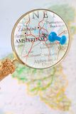 Looking in on Amsterdam, Holland. Blue tack on map of Benelux with magnifying glass looking in on Amsterdam, Holland Royalty Free Stock Photos