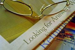 Looking for answers. Reading glasses and newspaper Royalty Free Stock Images