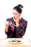 Looking anxiously at Japanese sticks attractive beautiful brunette woman sushi on the plate on white background isolated. Attractive beautiful brunette woman Royalty Free Stock Image