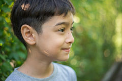 Looking away from the camera boy staning in front of the tree fence Royalty Free Stock Photo