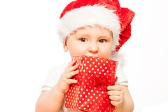 Looking baby in red Christmas hat with gift box Royalty Free Stock Photo