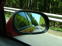 Looking back. A view from the right side-view mirror in a car, during the ride Stock Image