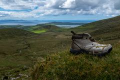 Looking back towards Dingle from the top of the Conor Pass on the Dingle Peninsula, Ireland, bright blue sky with fluffy clouds,. An old abandoned boot in the stock photography