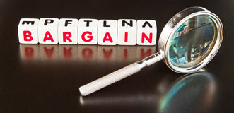 Looking for a bargain. Text ' bargain ' in red letters on small white cubes beside a hand magnifier, dark background Royalty Free Stock Image