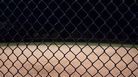 Looking at a baseball field at night through the fence. royalty free stock photos