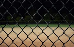 Looking at a baseball field at night through the fence. stock image