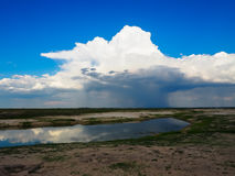 Looking at beautiful raining cloud from afar with blue sky backg. Round and water reflection during game drive in Chobe national park Stock Images