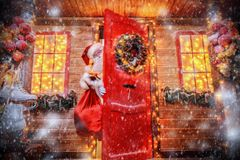 Looking from behind door. Christmas concept. Portrait of a fairytale Santa Claus looks out of the door of his house. Beautiful house decorated for Christmas royalty free stock image