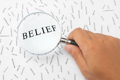 Looking for belief. The word, BELIEF is magnified Royalty Free Stock Images