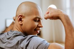 Young dark-skinned bodybuilder looking at his biceps royalty free stock photo