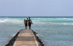 Looking For Big Waves. Two friends holding surfboards at the end of a long breakwater on Waikiki Beach, Oahu, Hawaii Royalty Free Stock Photography