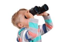 Looking through binoculars. Young boy explorer searching with binoculars Stock Photo