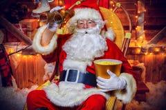 Looking through binoculars. Santa Claus sitting on his armchair eating popcorn, looking through binoculars. House of Santa Claus. Christmas decoration. Merry royalty free stock image