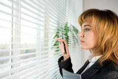 Looking through blinds. Profile of confident female looking outside through venetian blinds Royalty Free Stock Photos