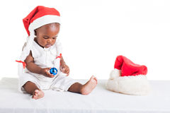 Looking at the blue ball. A 8 month old baby dressed to explore Christmas Stock Image