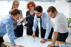 Looking at blueprint. Team of engineers discussing blueprint at meeting Stock Image