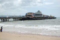Looking at Bourneouth pier which juts out into the sea from the beach. Stock Images