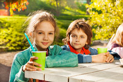 Looking boy and girl with green cups sit at table Stock Photos