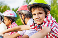Looking boy in helmet with African guys behind Royalty Free Stock Photo