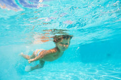 Looking boy moving while swimming undewater Stock Photo
