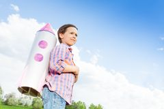 Looking boy wears paper rocket toy on shoulders Royalty Free Stock Photos