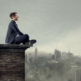 Looking for business opportunities. Businessman sitting on top of a building looking far away with cityscape on backgound Stock Image