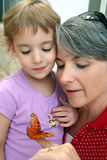 Looking at the Butterfly. A little girl and her grandmother look closely at a butterfly that sits on her finger Royalty Free Stock Image