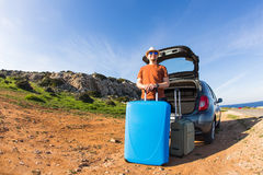 Looking at camera, a cheerful man going away for the weekend by the car with luggage Stock Images